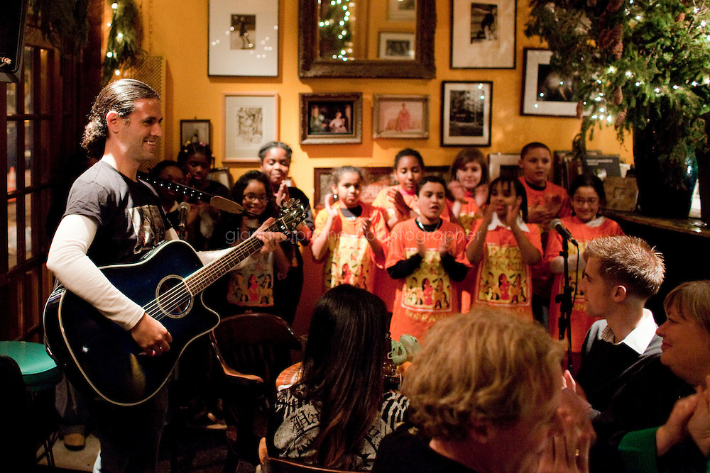 """18 December, 2008. New York, NY. Choir director Gregg Breinberg, 36, directs his fifth grade students from the Graniteville School chorus in Staten Island, at the Kitchen Club restaurant for a Bruce Weber private party in Manhattan, NY. <br /> <br /> The story of P.S. 22 Chorus began in the fall of 1999 when Breinberg arrived at the 1,250 student K-5 elementary school after being excised from his first music teaching job at nearby P.S. 60 in Staten Island.   Unfortunately for Mr. Breinberg, himself a Staten Island native, P.S. 22 didn't have any available music jobs so he found himself in the unfamiliar position of second grade teacher.<br /> <br /> """"It was never my intention to be a classroom teacher,"""" Breinberg dressed casually in a pair of blue jeans and grey sweatshirt, said.  """"In the absence of a music job, I used music to teach second grade. Everything I taught from math to english, I taught with music.""""<br /> ©2008 Gianni Cipriano for The New York Times<br /> cell. +1 646 465 2168 (USA)<br /> cell. +1 328 567 7923 (Italy)<br /> gianni@giannicipriano.com<br /> www.giannicipriano.com"""