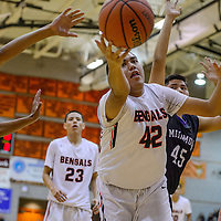 Gallup Bengal Troy Etistty (42) grabs a rebound away from Miyamura Patriots Ryan Smith (45) and Daquan Walker  (23) Friday at Gallup High School.