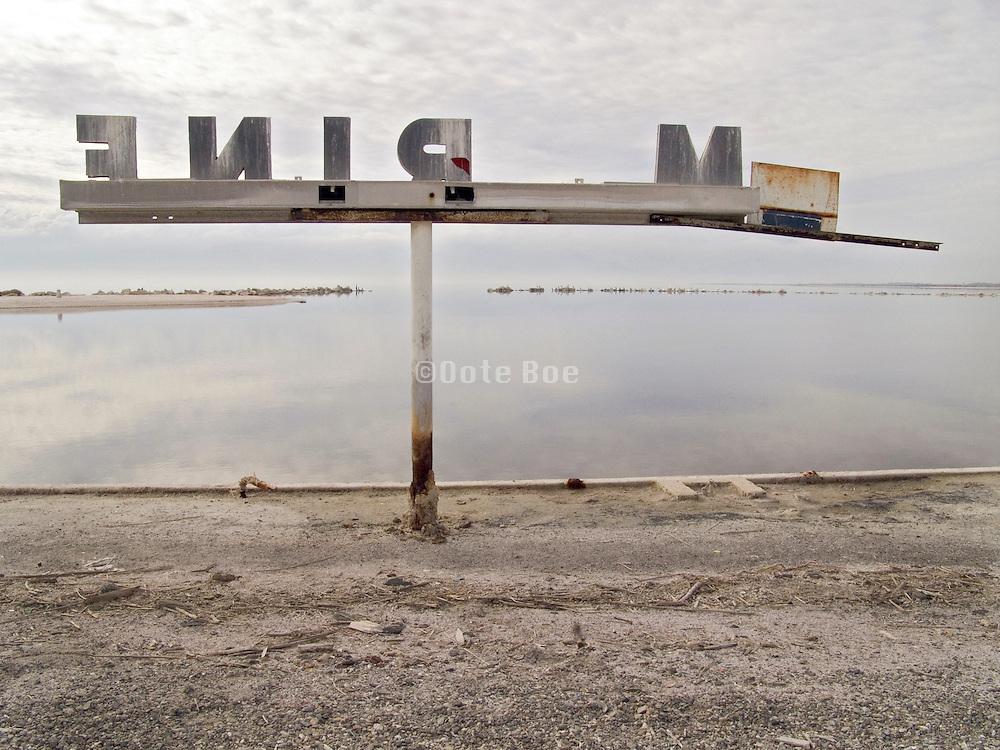 abandoned marina sign at the water edge