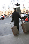 hotel porter bringing suitcases to a waiting car New York City