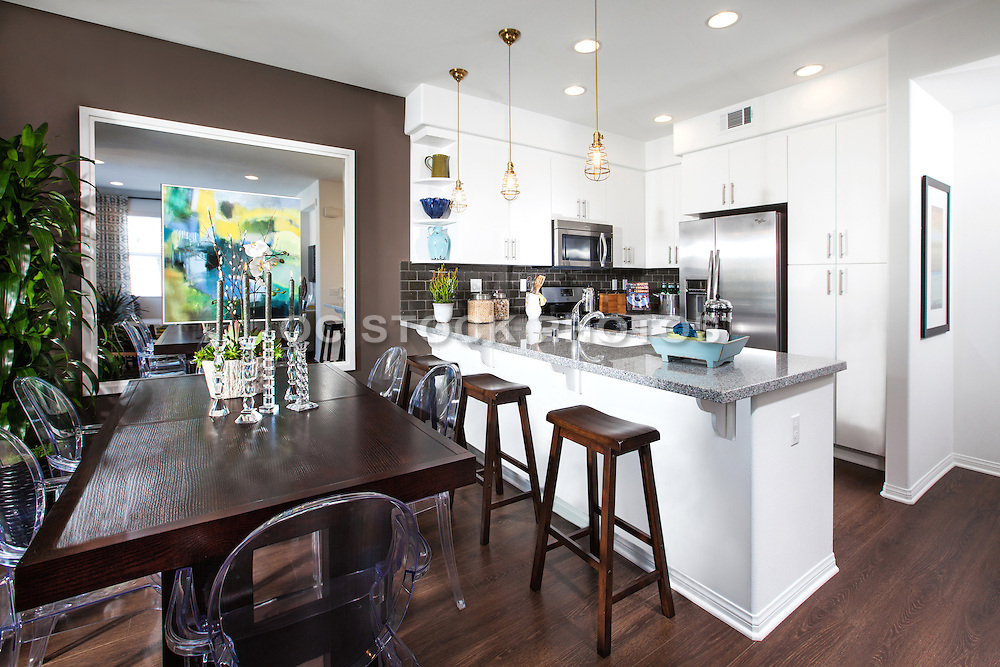 Dining Room and Kitchen with Dark Hard Wood Floors and Stainless Steel Appliances