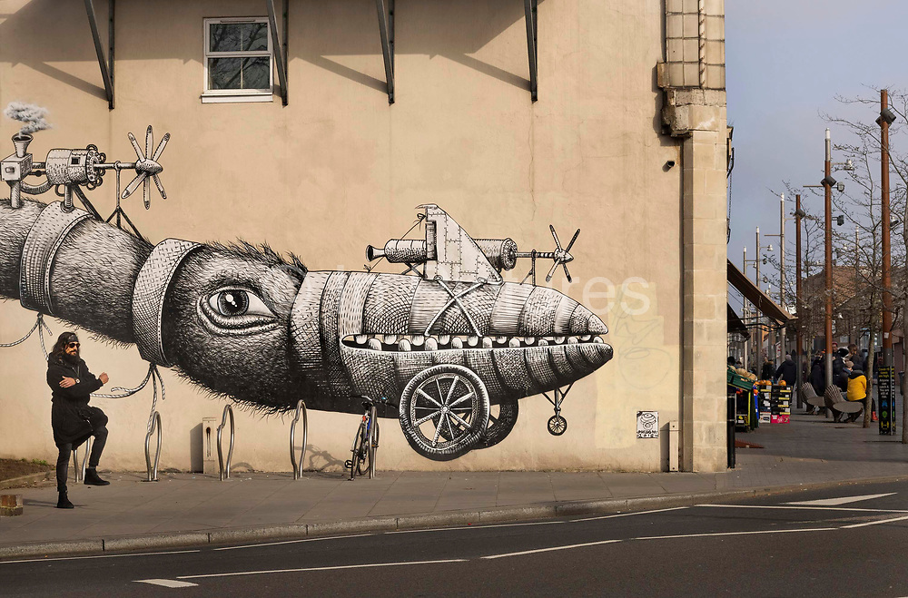 Man exercising in front of a mural by the artist Phlegm in Walthamstow market on 1st March 2021 in London, United Kingdom. The project was the culmination of consultations held with local residents who fed back that they would like to see artwork in the area. A panel made up of the Leader of the Council, representatives from a local charity, the Mill, local businesses, a local historian, and the St James Street Big Local made the final decisions in selecting artist Phlegm. Phlegms work depicts the triplane developed by Edwardian engineer, Alliott Verdon Roe who was based in one of the railway arches in Walthamstow Marshes.