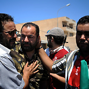 Three rebel fighters react to the news of their younger brother's death during combat for control of central Zawiyah.