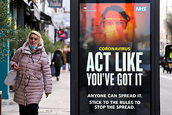 © Licensed to London News Pictures. 18/01/2021. London, UK. A woman wearing a protective face covering walks past the government's 'Act Like You've Got It' publicity campaign poster in north London, after the mutated variant of the SARS-Cov-2 virus continues to spread around the country. People in England aged 70 and over have started to receive offers of a coronavirus vaccine from today. The government could lift the lockdown in March, after people aged 70 and above have been vaccinated. Every adult in the UK will be offered a first dose of a coronavirus vaccine by September. Photo credit: Dinendra Haria/LNP
