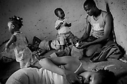 A group of migrants and their children rest in a corner of a house, where there is some shelter from the merciless sun in a desert in Morocco. Trying to flee war, violence and poverty in southern and western Africa, they have wound up in the clutches of human traffickers. Several of them have been held captive in the enclosure for up to three years.