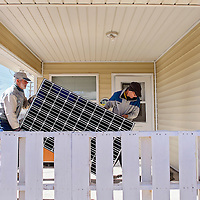 011014       Cable Hoover<br /> <br /> Gallup Solar representative Don Hyde, right, and Habitat for Humanity volunteer Dale Underwood carry solar panels onto the porch of Habitat for Humanity home in Gallup Friday.