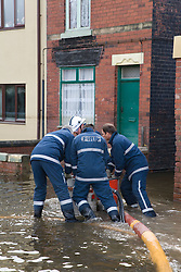 Members of the fire rescue service moving high volume pumps (HVP) used to drain away flood water and dump it into nearby rivers and lakes following the floods at Toll Bar; South Yorkshire; July 2007,