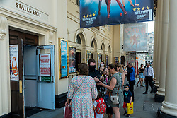 """© Licensed to London News Pictures. 19/07/2021. LONDON, UK. People line up for a matinee performance of The Tiger Who Came For Tea at the Haymarket Theatre on what has been dubbed """"Freedom Day"""", when the UK government has eased remaining coronavirus lockdown restrictions.  This comes against a backdrop of a rising number of daily positive cases, large numbers being required to self-isolate after being notified by the NHS app on their smartphones, including Boris Johnson, Prime Minister, Rishi Sunak, Chancellor, and Sajiv Javid, Health Secretary. The majority of theatres remain at 50% capacity and will gradually ease back to 100% over the next few weeks. Photo credit: Stephen Chung/LNP"""