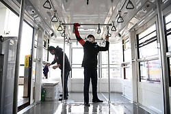 March 18, 2020, Chongqing, China:  Staff members disinfect a cable car in southwest China's Chongqing. The cableway across the Yangtze River reopened here Wednesday. (Credit Image: © Tang Yi/Xinhua via ZUMA Wire)