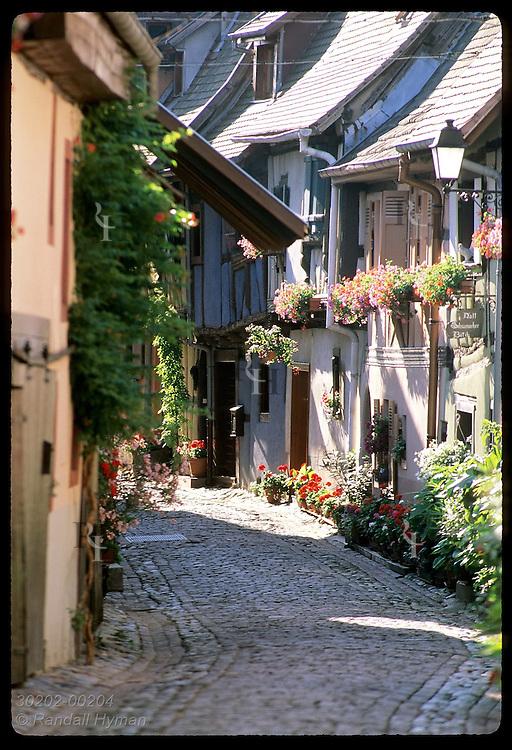 Flowers fill facades of half-timbered homes along cobblestone street; (v) Eguisheim, Alsace. France