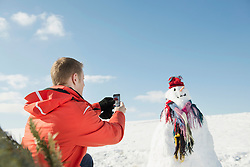 Man taking picture of snowman with smart phone, Bavaria, Germany