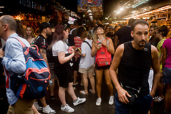 August 8, 2017 - Barcelona, Catalonia, Spain - Tourists visit La Boqueria market on August 8, 2017 in Barcelona, Spain. In the past year there have been a series of protests as residents complain that massive tourism and rising rents are driving them out of their city. Representatives of the hotel sector have expressed their concern about the recent attacks on tourist interests by anti-system groups that also coincide with a strike by Barcelona Airport security agents that are causing problems of mobility. (Credit Image: © Jordi Boixareu/NurPhoto via ZUMA Press)
