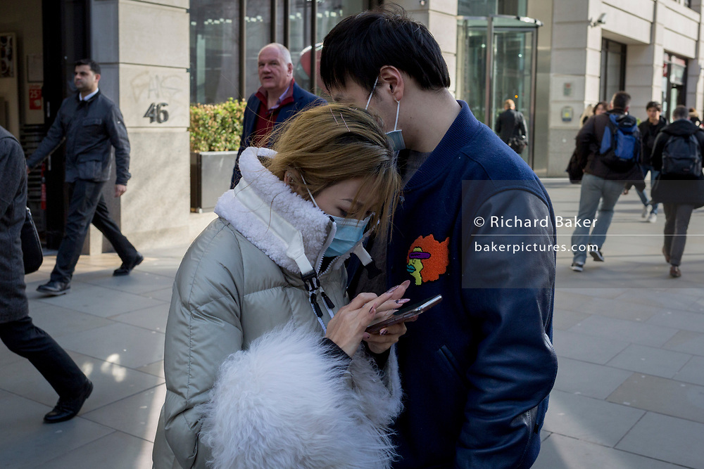 On the day that Chancellor of the Exchequer Rishi Sunak unveiled a £30bn package to boost the economy and get the country through the coronavirus outbreak, an Asian couple look at their phones on London Bridge in the capital's financial district, on 11th March 2020, in the City of London, England.