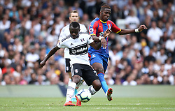 """Fulham's Jean Michael Seri (left) and Crystal Palace's Wilfried Zaha battle for the ball during the Premier League match at Craven Cottage, London. PRESS ASSOCIATION Photo. Picture date: Saturday August 11, 2018. See PA story SOCCER Fulham. Photo credit should read: Yui Mok/PA Wire. RESTRICTIONS: EDITORIAL USE ONLY No use with unauthorised audio, video, data, fixture lists, club/league logos or """"live"""" services. Online in-match use limited to 120 images, no video emulation. No use in betting, games or single club/league/player publications."""
