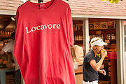 """A woman bites into fresh summer fruit beside a hanging T-shirt imprinted with the word """"Locavore"""" at Walker's Roadside Stand, Little Compton, Rhode Island."""