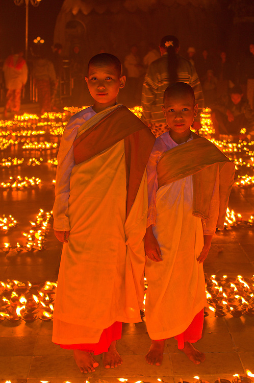 Two novice nuns surrounded by thousands of candles at the Golden Rock, Kyaikhtiyo Pagoda, Mon State, Myanmar (Burma)