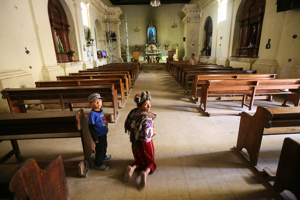 An indigenous woman walks on her knees down the aisle of the church in Nebaj, Quicke, Guatemala
