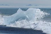 Stranded iceberg pounded by waves at Jökulsárlón, Iceland