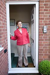 Older woman standing outside her front door,