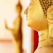 Golden statues of The Buddha (Siddhartha Gautama) at a Wat (Buddhist Temple) in Vientiane, Laos. This statue is in the Cambodian style. Focus is on the statue in the foreground with shallow depth of field.