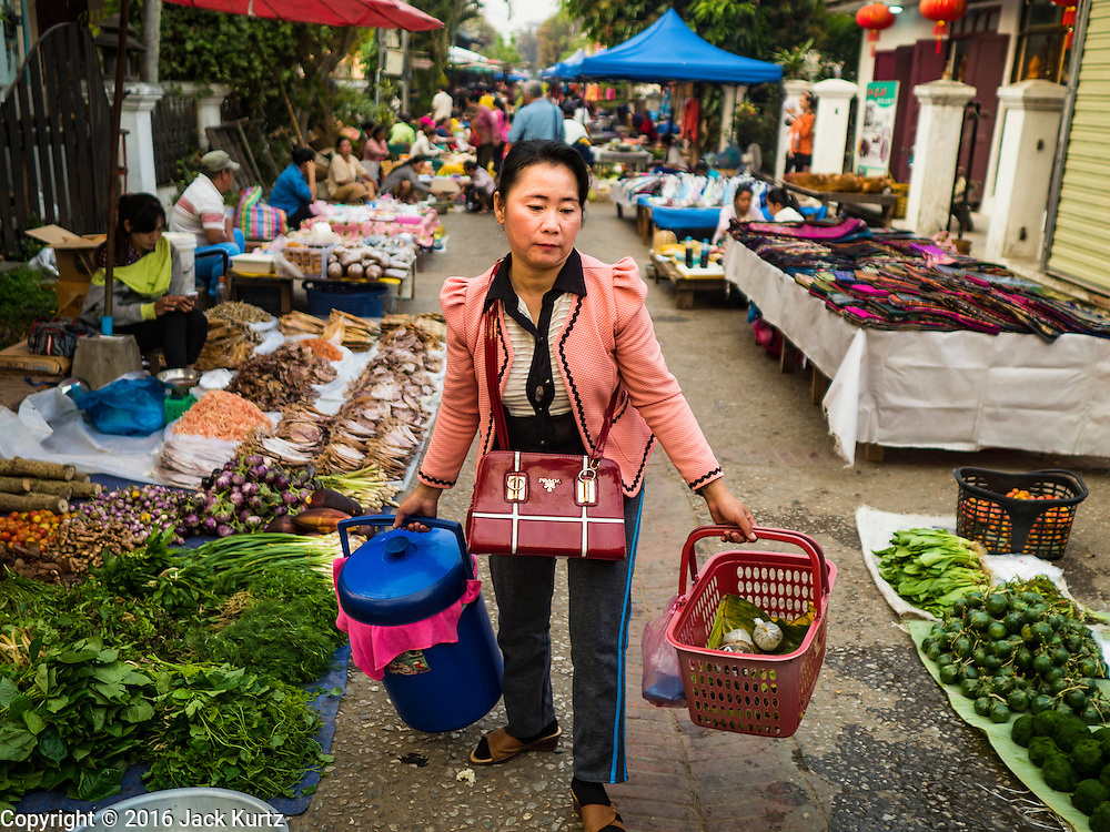 "13 MARCH 2016 - LUANG PRABANG, LAOS: A woman walks through the market in Luang Prabang. Luang Prabang was named a UNESCO World Heritage Site in 1995. The move saved the city's colonial architecture but the explosion of mass tourism has taken a toll on the city's soul. According to one recent study, a small plot of land that sold for $8,000 three years ago now goes for $120,000. Many longtime residents are selling their homes and moving to small developments around the city. The old homes are then converted to guesthouses, restaurants and spas. The city is famous for the morning ""tak bat,"" or monks' morning alms rounds. Every morning hundreds of Buddhist monks come out before dawn and walk in a silent procession through the city accepting alms from residents. Now, most of the people presenting alms to the monks are tourists, since so many Lao people have moved outside of the city center. About 50,000 people are thought to live in the Luang Prabang area, the city received more than 530,000 tourists in 2014.    PHOTO BY JACK KURTZ"