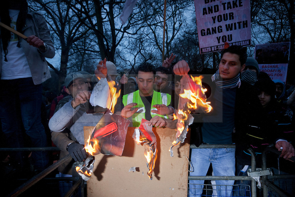 © licensed to London News Pictures. London, UK 18/02/2012. A group of protesters burning Bashar al Assad's poster outside Syrian Embassy in London, after Islamist group Hizbut Tahrir marched to Syrian Embassy in London to protest against Bashar al Assad's regime. Photo credit: Tolga Akmen/LNP