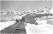 """A winter view of RGS snowshed and section house at Lizard Head from atop a northbound freight train caboose.  Photo is captioned """"Phillips hands up orders at Lizard Head"""".<br /> RGS  Lizard Head, CO  Taken by Rasmussen, Forest - ca. 1948<br /> In book """"Rio Grande Southern II, The: An Ultimate Pictorial Study"""" page 273<br /> Also at RD137-056."""