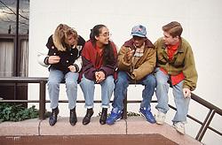 Multiracial group of teenagers sitting on metal railings talking,