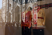 Mens' clothing in shop window and reflection of Florence's Duomo cathedral.
