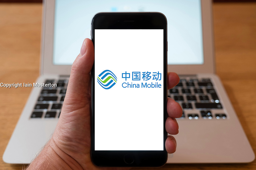 Using iPhone smartphone to display logo of China Mobile the Chinese state-owned telecommunication company