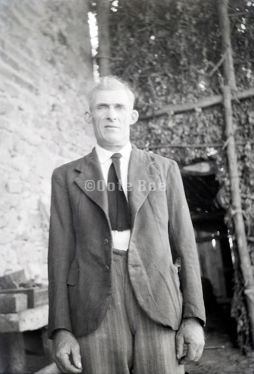 mature adult male a little uncomfortable standing in a barn 1950s