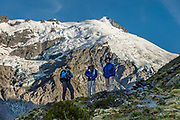Three trampers are silhouetted against glacier-clad Mt Edward (2620m) in Dart Valley on a spectacular day hike from Dart Hut to Cascade Saddle. Rees-Dart Track, in Mount Aspiring National Park, Otago region, South Island of New Zealand. At lower left is Hesse Glacier.