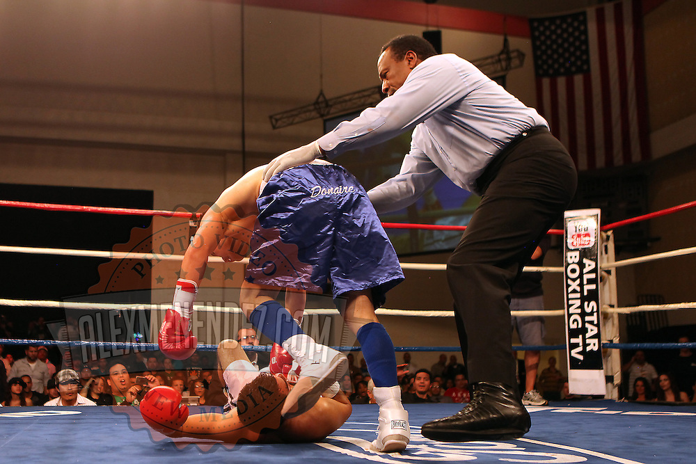 """Former WBO World champion Alex """"El Nene"""" Sanchez (White Trunks) of Ponce, Puerto Rico holds onto Glen Donaire (Blue Trunks) after being knocked down in round 2  at the Kissimmee Civic Center in Kissimmee, Florida, on Friday, Dec 9, 2011.  Donaire won the bout when Sanchez injured his left wrist and failed to come out in the ninth round. (AP Photo/Alex Menendez)"""