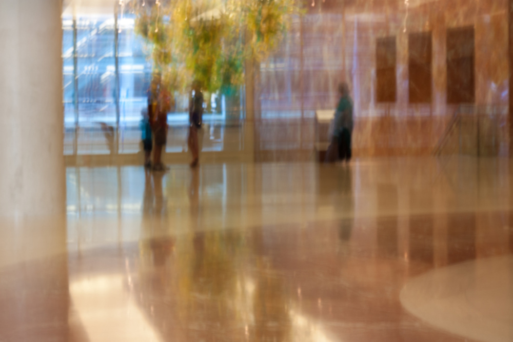 People in an urban building interior rendered with intentional camera movement.