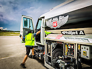 A Phillips 66 Aviation Fuels lineman mounts his vehicle at Opa-locka Executive Airport, near Miami.  Commissioned as an advertising image.  <br /> <br /> Created by aviation photographer John Slemp of Aerographs Aviation Photography. Clients include Goodyear Aviation Tires, Phillips 66 Aviation Fuels, Smithsonian Air & Space magazine, and The Lindbergh Foundation.  Specialising in high end commercial aviation photography and the supply of aviation stock photography for advertising, corporate, and editorial use.