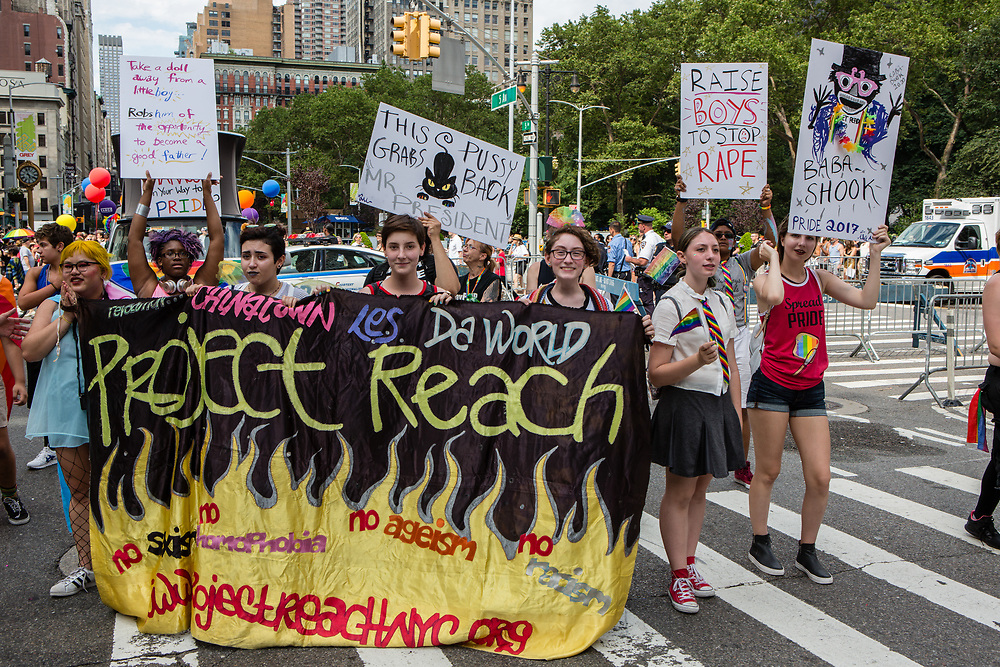 """New York, NY - 25 June 2017. New York City Heritage of Pride March filled Fifth Avenue for hours with groups from the LGBT community and it's supporters. Marchers from Project Reach, which fights injustice. One marcher carries a sign reading """"This pussy grabs back Mr. President."""""""