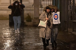 © Licensed to London News Pictures. 20/10/2021. London, UK. Members of the public shelter under a coat as they walk during heavy rain in Greenwich South East London. An Amber weather warning for rain is in place for parts of London and South East England.  Photo credit: George Cracknell Wright/LNP