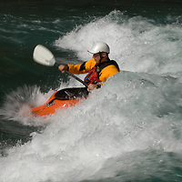 Kayaker Jeff Germaine plays in waves on the  Kananaskis River in the Canadian Rockies near Calgary, Alberta.