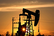 A CNPC 'nodding donkey' oil pump at sunset in an oilfield outside Daqing, Heilongjiang province, China, on July 13, 2006.  China National Petroleum Corp is the mother company of PetroChina. Photo by Servais Mont/Pictobank