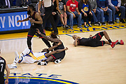 Golden State Warriors and Houston Rockets bodies hit the floor for a loose ball at Oracle Arena in Oakland, Calif., on March 31, 2017. (Stan Olszewski/Special to S.F. Examiner)