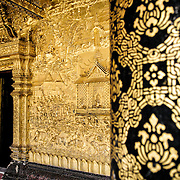 A black and gold column at right with the intricate gold exterior walls at Wat Mai Suwannaphumaham.  Wat Mai, as it is often known, is a Buddhist temple in Luang Prabang, Laos, located near the Royal Palace Museum. It was built in the 18th century and is one of the most richly decorated Wats in Luang Prabang.