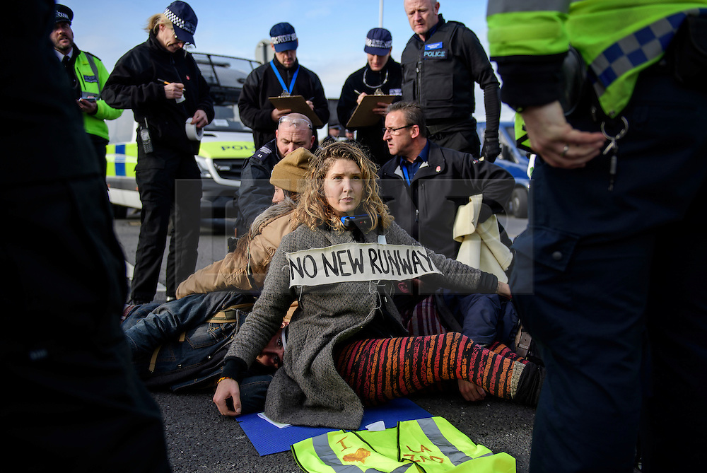 """© Licensed to London News Pictures. 19/11/2016. Heathrow, UK. An activist wearing the slogan """"NO NEW RUNWAY"""" sits on the road surface, that she and other activists are attached to, near Heathrow Airport. A group of activists stage attach themselves to a road surrounding  Heathrow Airport, during a demonstration against the expansion of Heathrow Airport and the building of a third runway. Some activists  threatened """"direct action"""". Photo credit: Ben Cawthra/LNP"""