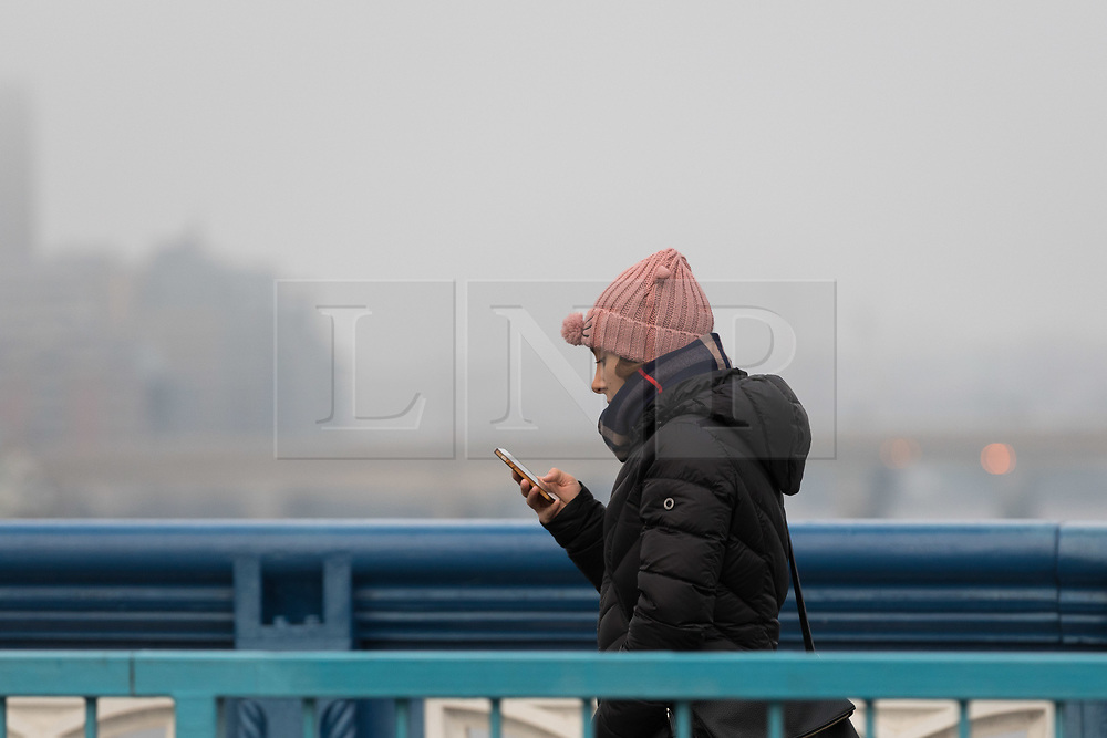 © Licensed to London News Pictures. 17/12/2017. London, UK. A woman walks across Tower Bridge during freezing fog this morning. The capital experienced another very cold night with freezing weather. Photo credit: Vickie Flores/LNP