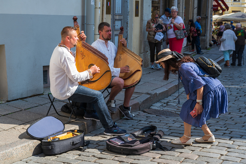 Tallinn, Estonia -- July 23, 2019. A tourist makes a donation to street musicians playing in a shopping area.