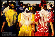 Women in traditional dress walk away at sunset thru crowds at the Feria de Abril festival; Seville Spain