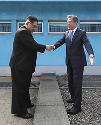 April 27, 2018 - Panmunjom, KOREA - North Korean leader Kim Jong Un, left, shakes hands with South Korean President Moon Jae-in over the military demarcation line at the border village of Panmunjom in Demilitarized Zone Friday, April 27, 2018. Their discussions will be expected to focus on whether the North can be persuaded to give up its nuclear bombs. (Credit Image: © Prensa Internacional via ZUMA Wire)