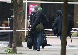 © London News Pictures. 27/04/2012. London, UK. Police snipers carrying guns away from the scene on Tottenham Court Road in Central London following reports of a hostage situation..  Photo credit : Ben Cawthra /LNP