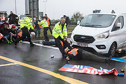 A Metropolitan Police officer drags Insulate Britain climate activist Reverend Tim Hewes across a M25 slip road at Junction 14 close to Heathrow airport which he had blocked as part of a campaign intended to push the UK government to make significant legislative change to start lowering emissions on 27th September 2021 in Colnbrook, United Kingdom. The activists are demanding that the government immediately promises both to fully fund and ensure the insulation of all social housing in Britain by 2025 and to produce within four months a legally binding national plan to fully fund and ensure the full low-energy and low-carbon whole-house retrofit, with no externalised costs, of all homes in Britain by 2030.