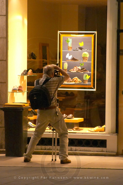A photographer taking a picture at night of a shoe shop window display with a back pack and tripod on the Cours de l'Intendence  city  Bordeaux Gironde Aquitaine France