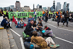 London, UK. 7 October, 2019. Climate activists from Extinction Rebellion and a line of Metropolitan Police officers block the approach to Lambeth bridge on the first day of International Rebellion protests to demand a government declaration of a climate and ecological emergency, a commitment to halting biodiversity loss and net zero carbon emissions by 2025 and for the government to create and be led by the decisions of a Citizens' Assembly on climate and ecological justice.